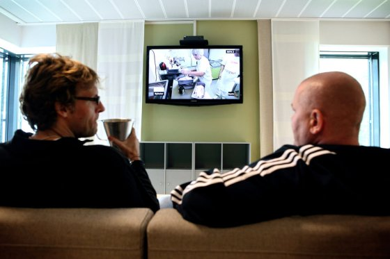 Two inmates are watching a television program in one of the common kitchen and living room areas established to be a meeting point between inmates and guards and to facilitate rehabilitation inside the luxurious Halden Fengsel, (prison) near Oslo.
