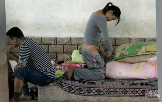A Chinese woman injects herself in the thigh with drugs under a Shenzhen overpass.