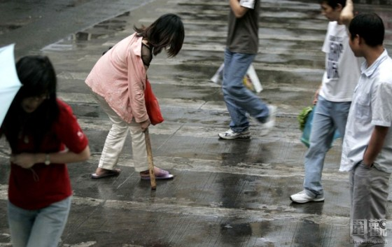 A Chinese woman and drug addict walking with a stoop after Shenzhen police drove her and other drug users out from under an overpass that was a popular gathering place for drug addicts.