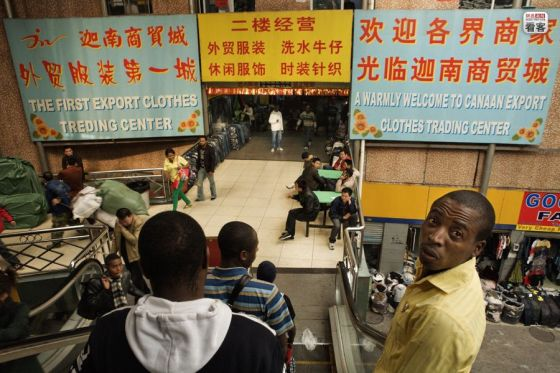 Africans in Guangzhou, China, entering the Canaan Clothing Market.