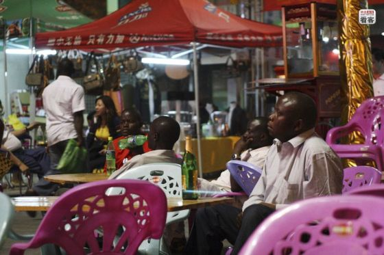 Africans seated at the tables of a street side food stall.