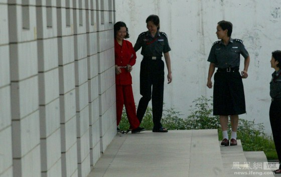 A condemned Chinese woman is led out of her prison cell by prison guards in Wuhan, China, on her way to her execution.