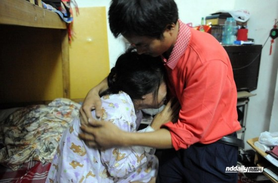 Husband Yang Wu holds wife Wang Juan in his arms, both crying.
