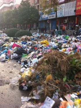 Piles of garbage on the streets of Nanjing, China as city sanitation workers protest unmet wage increases.