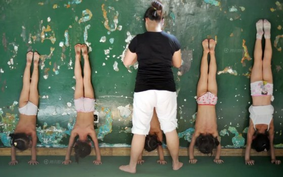 Chinese children doing handstands for gymnastics training.