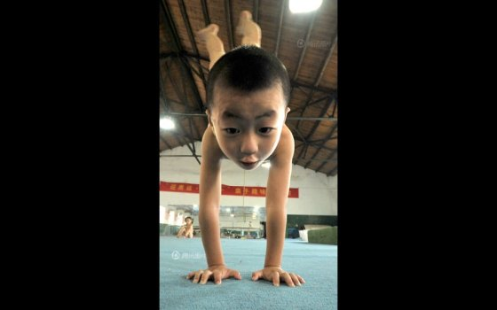 A Chinese boy doing a handstand during gymnastics training.