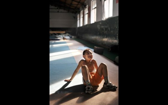 A Chinese boy relaxing after gymnastics training.