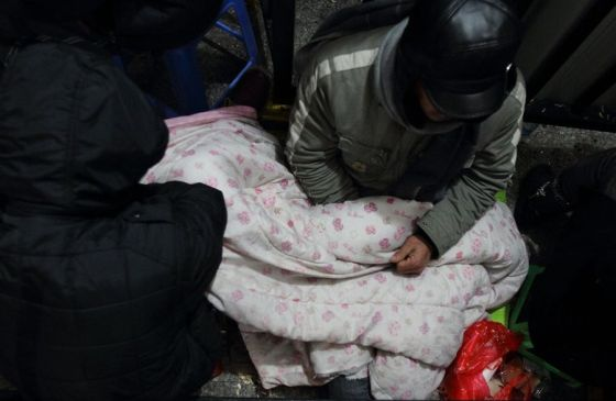 A Chinese migrant worker asleep on the ground waiting in line overnight to buy train tickets home for the holidays.
