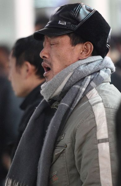 Li Zhuqing, a Chinese migrant worker who has waited 6 days and 6 nights to buy train tickets home for the holidays, yawns in line.