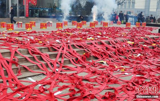 Boxes of fireworks and long strings of firecrackers in front of a Chinese company.