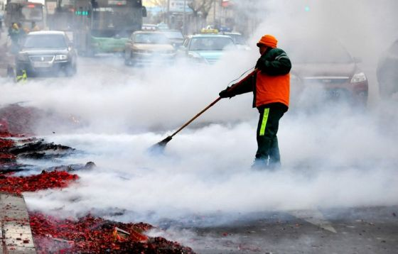 A Chinese sanitation worker sweeps up the red husks of used firecrackers that cover the streets of China during Chinese New Year.