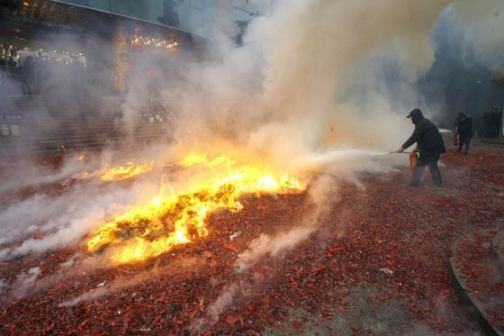 A fire burns over the litter of firecrackers.