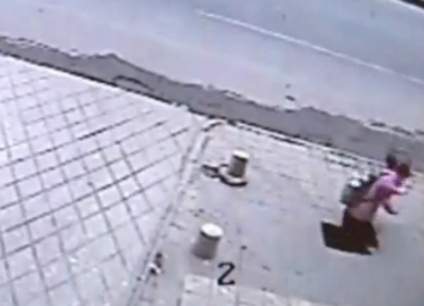 A Chinese girl suddenly falls through the sidewalk in Xi'an, China.