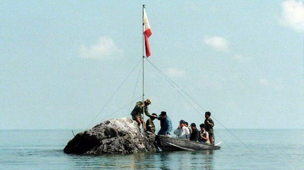 Filipinos plant a Philippine flag on a rock by the Scarborough Shoal.