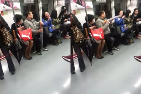 An elderly Korean man tries to stop a young Korean woman smoking on the subway with his umbrella.