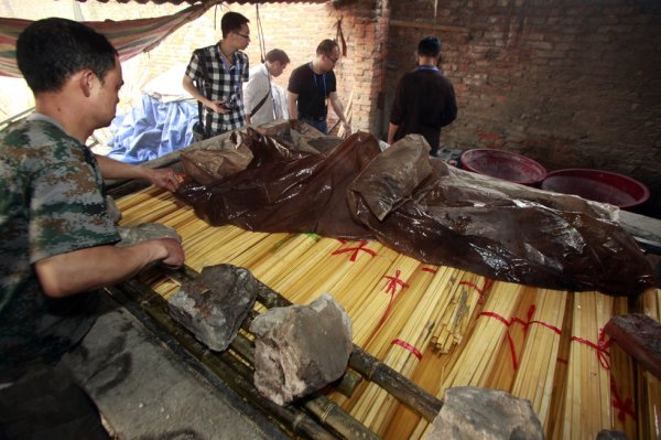 Law enforcement and journalists investigate a disposable chopsticks manufacturing plant in Guangxi, China.