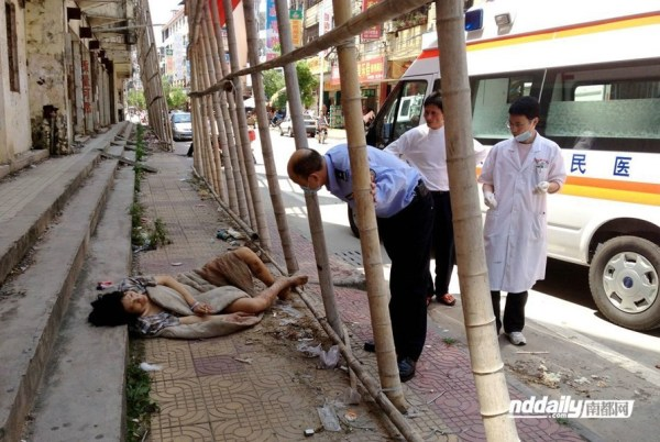 A Chinese police officer and medical personnel stand next to drug addict Wu Guilin lying on the open street, his body too weak to walk.
