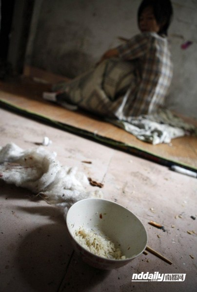 A bowl of dried leftover rice near Wu Guilin's mat that serves as his bed.