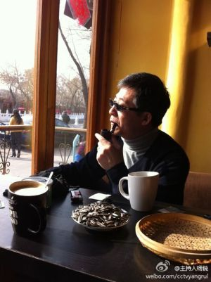 CCTV International presenter Yang Rui smoking pipe in coffee shop.
