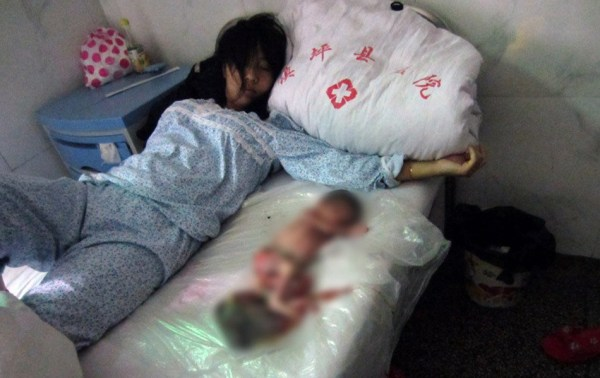 A Chinese mother lying on a hospital bed with her aborted 7-month-old fetus beside her.