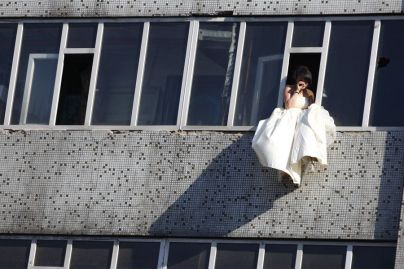 Distraught Chinese bride on window sill.