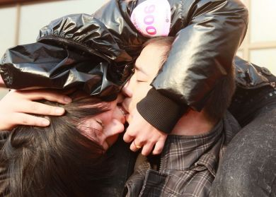 Young Chinese couple in kissing competition.