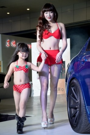 A little Chinese girl and her mother participating in a modeling competition at a car show in Wuhan, China.