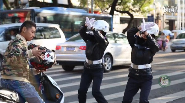 Two female Chinese traffic police officers stop a motorscooter rider on the street to remind him to wear a helmet, in a music dance video released on December 2nd to promote traffic safety awareness.