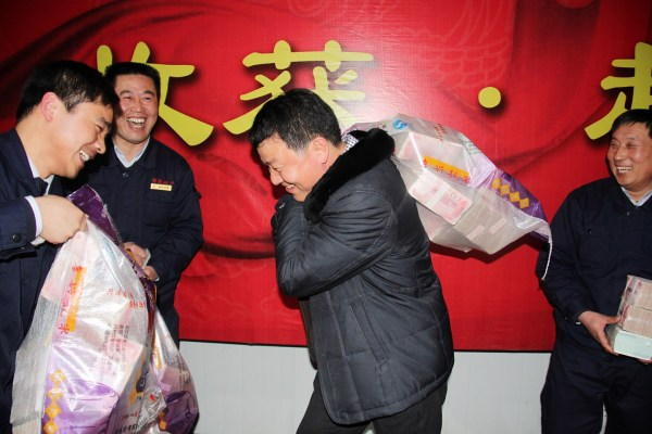 Henan Chinese real estate company employees carry home year-end cash bonuses in burlap sacks.