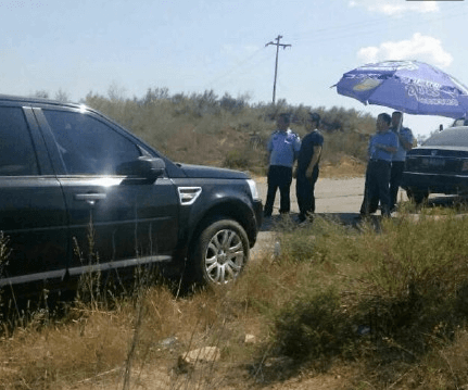 Policeman Puts Up Parasol For Fire Inspecting Official