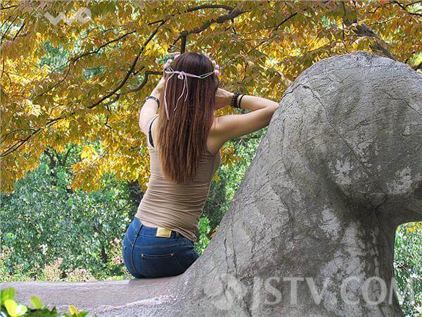 Young Female Tourist Sits On Cultural Relic To Take Selfies