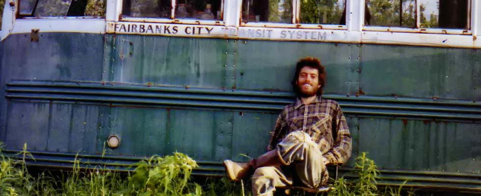 A self portrait of Chris McCandless in front of the bus he used as a shelter