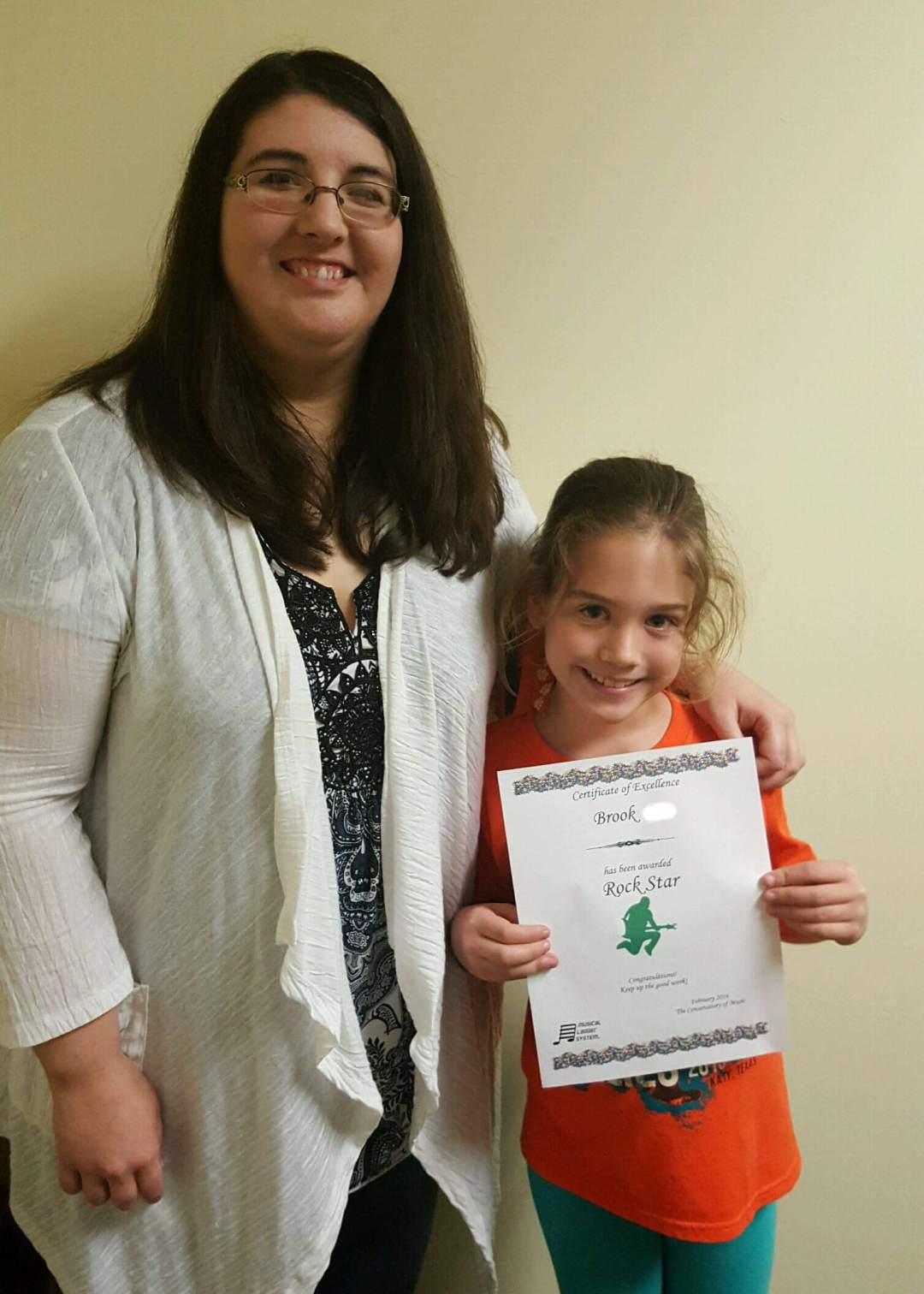 Girl receiving award at piano lesson in Katy