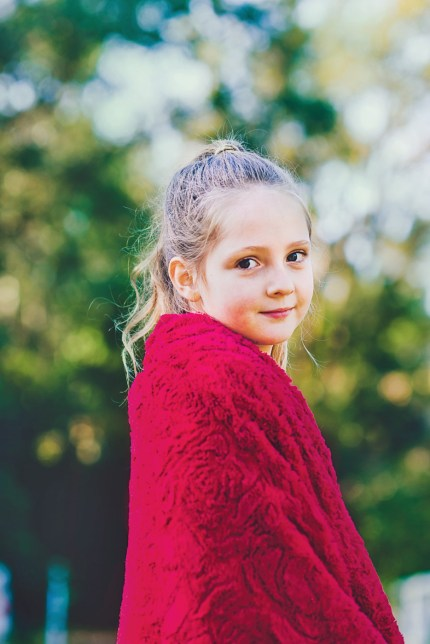 Sydney family photographer/a girl wrapped in a red blanket.
