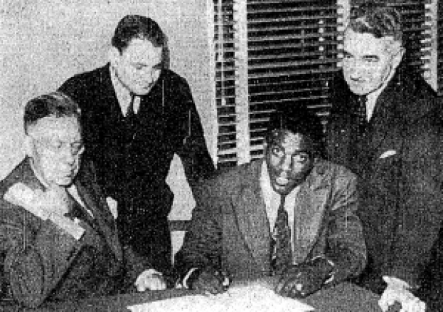 Robinson signing contract with the Montreal Royals in 1945 as Royals President Hector Racine, Branch Rickey Jr. and Royals Vice-President Romeo Gauvreau look on.