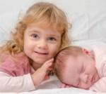 portrait-d-une-petite-fille-avec-sa-soeur-agee-de-15-jours