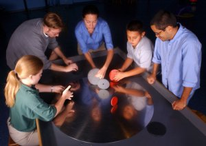 Visitors play with the physics of orbiting, finding that spinning a disk on its side prolongs the time and distance of the orbit.
