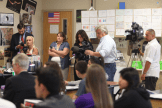 Newspaper and television reporters record the action.