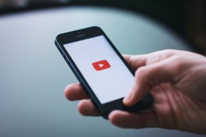 YouTube logo on a phone being held by a hand