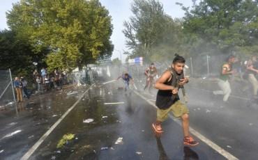 """Subotica, 16.9.2015 - Nekoliko stotina izbjeglica probilo je u srijedu oko 15 sati ogradu od bodljikave žice na granici prema Srbiji, zbog èega je policija upotrijebila suzavac i vodene topove, dovozi oklopna vozila i rasporeðuje snage opremljene za razbijanje prosvjeda. Izbjeglice su na jednom mjestu na graniènom prijelazu """"Horgoš 2"""" probile ogradu, prosvjeduju i gaðaju policiju plastiènim bocama.  foto HINA/ TANJUG / NEMANJA JOVANOVIC / ua"""