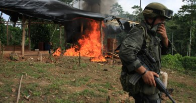 stand on guard after burning a coca laboratory near Tumaco, Colombia, in the southwest  state of Narino, June,8, 2008, According to the Police  nearly 30,000 hectares (75,000 acres) of coca fields have been fumigated and more than 130 laboratories destroyed in the south of the country since January. Colombia produces most of the world's cocaine. (AP Photo/William Fernando Martinez)