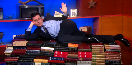Stephen Colbert lying on books