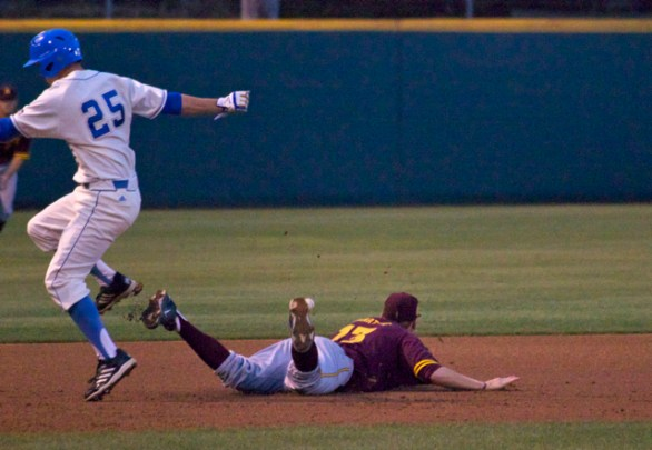 Chris Keck jumps over Dalton Dinatale, who can't make a diving stop on a grounder.