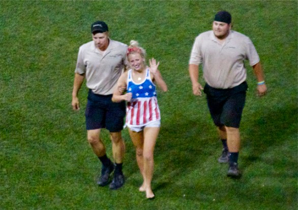 Abby Goetz gets escorted off for stupidly storming the field. (Photo: Shotgun Spratling)