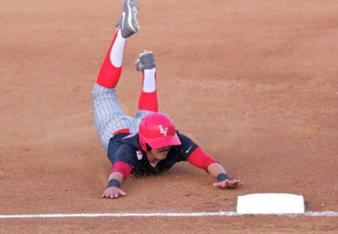 Edgar Montes dives into third base, feet flying. (Photo: Shotgun Spratling)