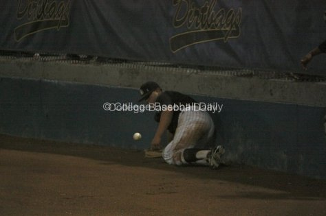 First baseman Ino Patron slides into the wall attempting to catch a pop up.