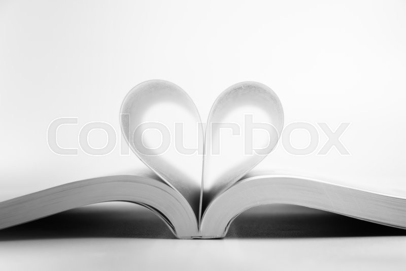 Opened book with heart page against blank background Stock Photo - opened book