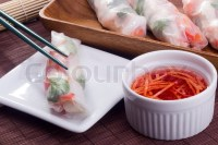 Asian spring roll in rice paper on a white plate and red ...