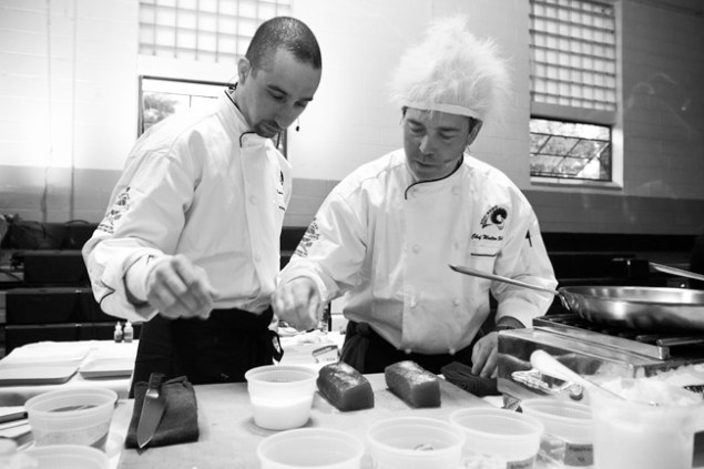 Basketball coach Shaka Smart (left) and Lemaire executive chef Walter Bundy (right) prepare tuna at the Coach's Cook-Off. Photo by Zoë Dehmer.