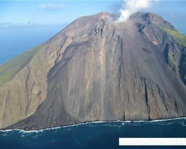 Figura 2 - La foto mostra il fianco settentrionale dello Stromboli, con i crateri che degassano nella parte alta del vulcano (dove si vede la nube bianca di gas). Alla sinistra della foto si nota il campo lavico che si è formato durante l'eruzione del 2007 lungo il fianco orientale della Sciara del Fuoco. (Foto di Sonia Calvari)